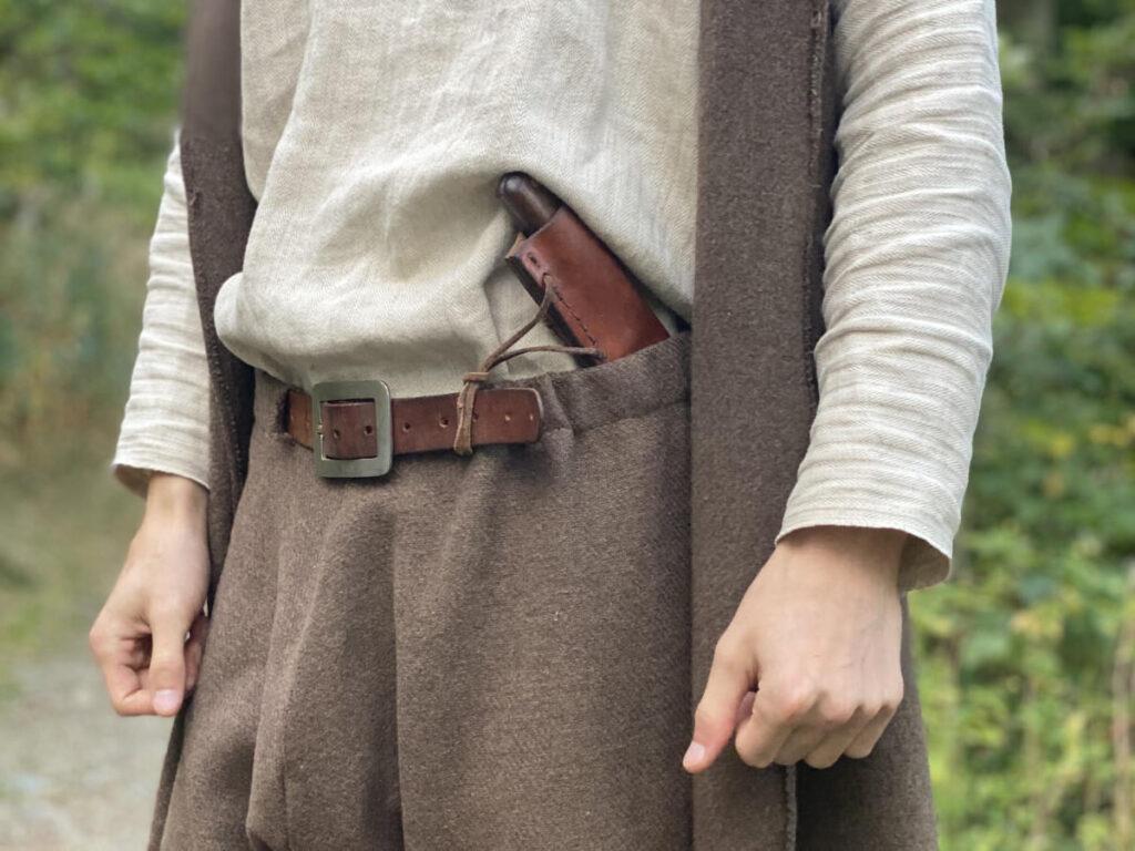Adrean mit selbst gemachter Kleidung und Messer im Hosenbund