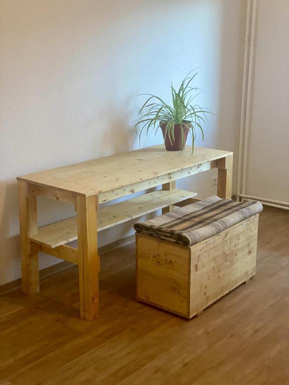 Minimalistischer, selbst gebauter Tisch mit Truhe und Wolldecke